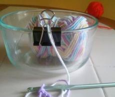 Use a binder clip on the edge of a bowl to dispense yarn