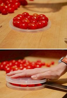 Use two plastic lids to easily cut cherry tomatoes in half