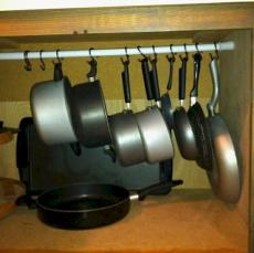 Use a tension rod to hang pots and pans